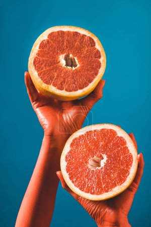 Photo for Cropped view of woman holding grapefruit halves in coral colored hands on blue background, color of 2019 concept - Royalty Free Image