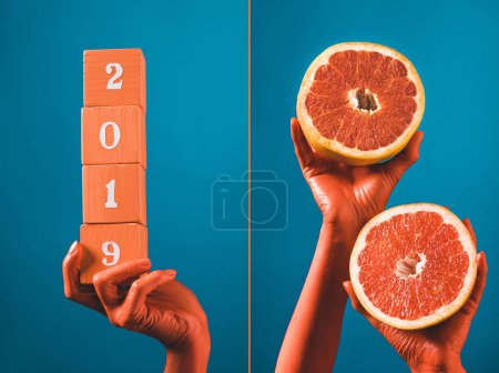 Photo for Collage with wooden cubes with 2019 numbers and grapefruit halves in coral colored female hands on blue separated background, color of 2019 concept - Royalty Free Image