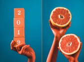 collage with wooden cubes with 2019 numbers and grapefruit halves in coral colored female hands on blue separated background, color of 2019 concept