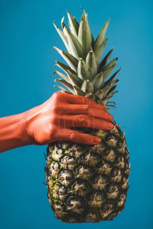 Photo for Cropped view of woman holding pineapple in coral colored hand on blue background, color of 2019 concept - Royalty Free Image