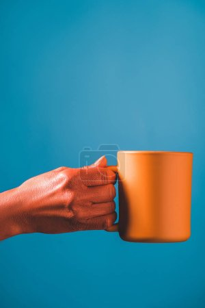 Photo for Partial view of coral colored female hand and cup on blue background, color of 2019 concept - Royalty Free Image
