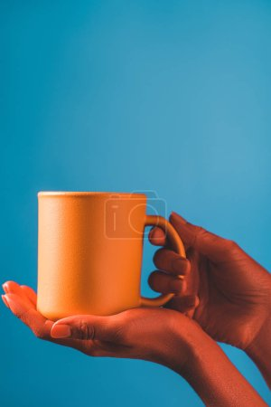 Photo for Cropped view of woman holding coral coffee cup on blue background, color of 2019 concept - Royalty Free Image