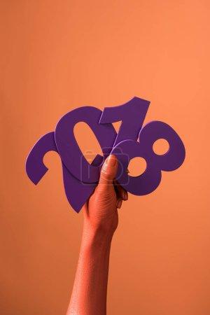 Photo pour Vue partielle des mains de femmes couleurs corail avec papier violet coupé 2018 numéros sur fond corail, couleur du concept de 2019 - image libre de droit