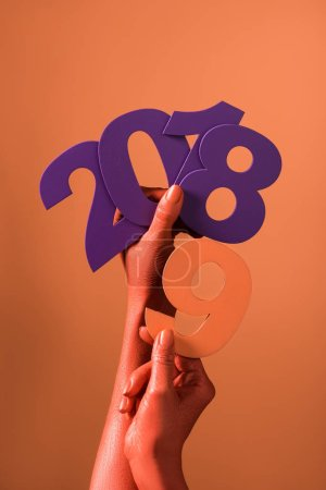 Photo for Partial view of coral colored female hands with violet paper cut 2018 numbers and coral number 9 on coral background, color of 2019 concept - Royalty Free Image