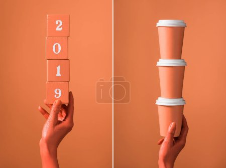 Photo for Coral wooden cubes with 2019 numbers and stack of coral paper cups in female hands on divided coral background, color of 2019 concept - Royalty Free Image