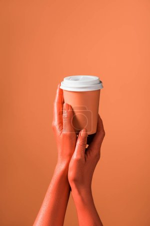 Photo for Cropped view of woman holding coral paper cup on coral background, color of 2019 concept - Royalty Free Image