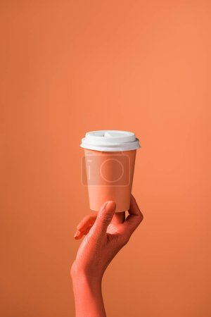 Photo for Partial view of female hand with coral paper cup on coral background, color of 2019 concept - Royalty Free Image