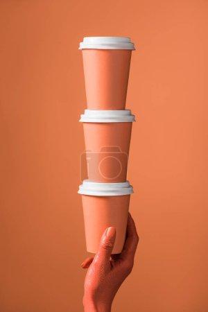 Photo pour Vue recadrée de la main féminine avec pile de gobelets en papier corail sur fond corail, couleur du concept 2019 - image libre de droit