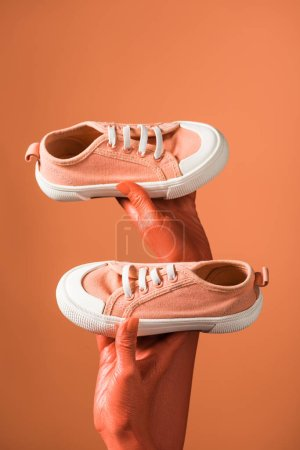 Photo for Cropped view of woman holding sneakers on coral background, color of 2019 concept - Royalty Free Image