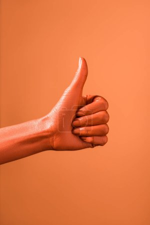 Photo for Cropped view of woman showing thumb up on coral background, color of 2019 concept - Royalty Free Image