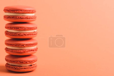 Photo for Stack of coral macarons on coral background with copy space, color of 2019 concept - Royalty Free Image