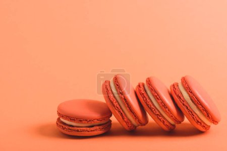 Photo for Tasty macarons on coral background, color of 2019 concept - Royalty Free Image