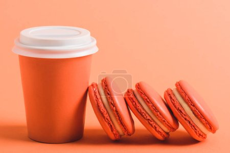 Photo for Delicious coral macarons and paper cup on coral background, color of 2019 concept - Royalty Free Image