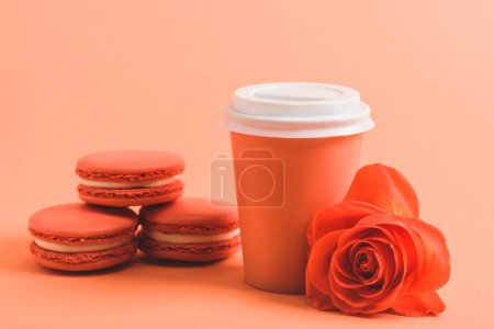 Photo for Delicious macarons and paper cup on coral background, color of 2019 concept - Royalty Free Image