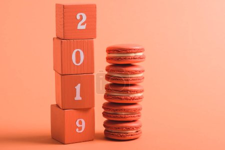 Photo for Stack of wooden cubes with 2019 numbers and macarons on coral background, color of 2019 concept - Royalty Free Image