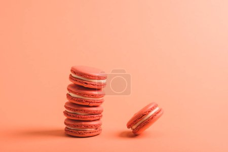 Photo for Tasty coral macarons on coral background, color of 2019 concept - Royalty Free Image