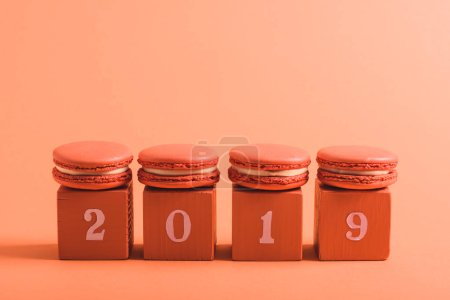 Photo for Coral cubes with 2019 numbers and macarons on coral background, color of 2019 concept - Royalty Free Image