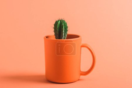 Photo for Green cactus in coral coffee cup on coral background, color of 2019 concept - Royalty Free Image