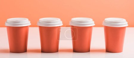 Photo for Coral disposable cups on coral background, color of 2019 concept - Royalty Free Image