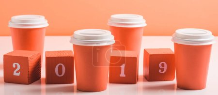 Photo for Coral wooden cubes with 2019 numbers and paper cups on white surface, color of 2019 concept - Royalty Free Image