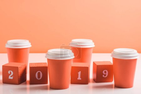 Photo for Coral disposal cups and wooden cubes with 2019 numbers and paper cups on white surface, color of 2019 concept - Royalty Free Image
