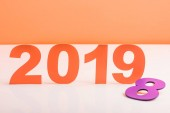 coral paper cut 2019 numbers and violet number 8 on white surface, color of 2019 concept