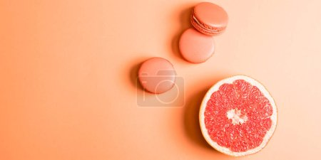 top view of coral macarons and grapefruit half on coral background, color of 2019 concept