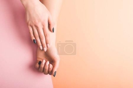 Foto de Vista recortada de las manos con uñas Rosa y negro sobre fondo bicolor, color del concepto 2019 - Imagen libre de derechos