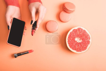 Photo for Cropped view of woman holding smartphone and coral lipstick, macarons and grapefruit half on coral background, color of 2019 concept - Royalty Free Image