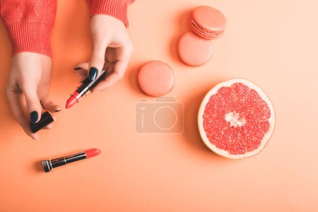 Photo for Cropped view of woman holding coral lipstick, macarons and grapefruit half on coral background, color of 2019 concept - Royalty Free Image
