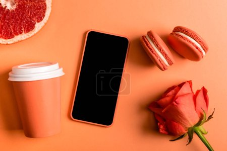 Photo for Smartphone in coral case, coral paper cups, rose flower, macarons and grapefruit half on coral background, color of 2019 concept - Royalty Free Image