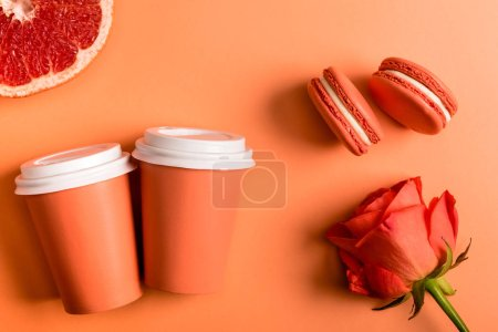 Photo for Coral paper cups, rose flower, macarons and grapefruit half on coral background, color of 2019 concept - Royalty Free Image