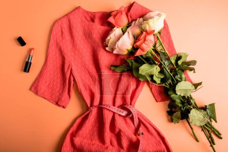 coral dress, roses bouquet and coral lipstick on coral background, color of the year 2019 concept