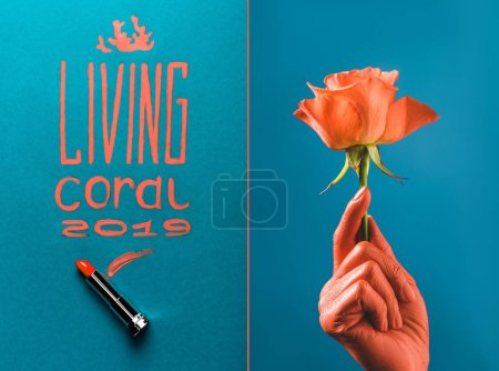color of year 2019 handwritten lettering with coral lipstick, and partial view of coral colored female hand with coral rose on blue divided background
