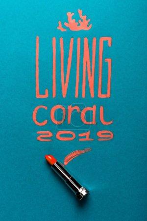 Photo pour Couleur de l'année 2019 lettrage manuscrit avec rouge à lèvres corail sur fond bleu - image libre de droit