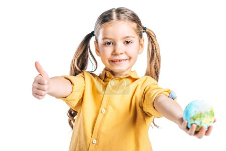 Photo for Smiling kid holding globe model and showing thumb up isolated on white, earth day concept - Royalty Free Image