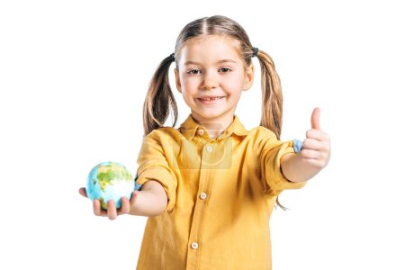 Photo for Cute child holding globe model and showing thumb up isolated on white, earth day concept - Royalty Free Image