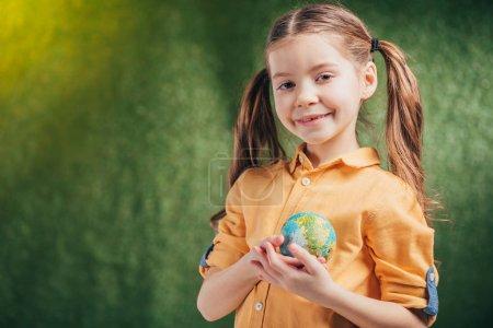Foto de Lindo niño sonriente que sostiene modelo globo cerca de corazón sobre fondo borroso, concepto de día de la tierra - Imagen libre de derechos