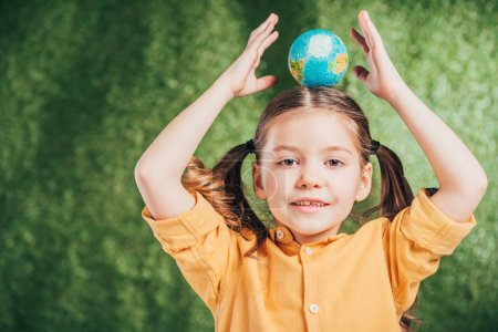 adorable kid holding globe model on head on blurred background, earth day concept
