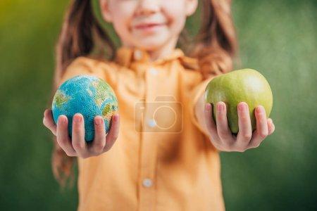 Foto de Enfoque selectivo del niño que sostiene el modelo globo y manzana sobre fondo borroso, concepto de día de la tierra - Imagen libre de derechos
