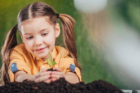 Photo pour Accent sélectif de la plantation d'enfants jeune plante sur fond flou, concept de jour de la terre - image libre de droit