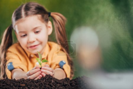 selective focus of cute kid planting young plant on blurred background, earth day concept