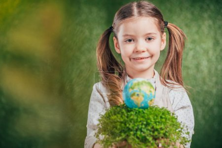 Photo for Selective focus of smiling child with flower pot and globe model on blurred background, earth day concept - Royalty Free Image