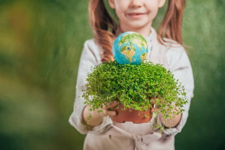 selective focus of kid holding flower pot with plant and globe model on blurred background, earth day concept