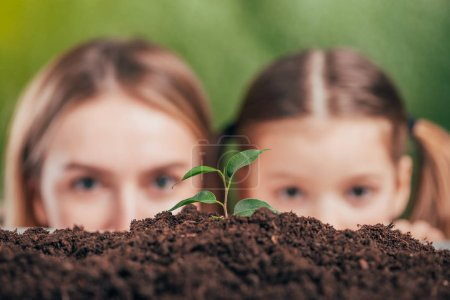 selective focus of woman and girl looking at young growing plant on blurred background, earth day concept