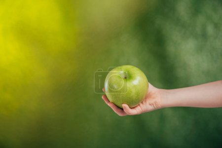 Photo for Partial view of child hand with apple on blurred background, earth day concept - Royalty Free Image