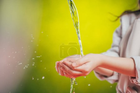 Photo for Selective focus of kid holding hands under flowing water on blurred background, earth day concept - Royalty Free Image