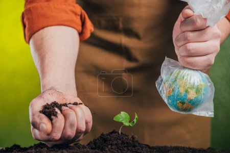 selective focus of man holding globe model in plastic bag and plating young green plant on blurred background, earth day concept
