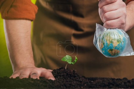 selective focus of man planting young plant and holding globe model in plastic bag on blurred background, earth day concept