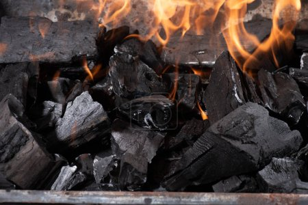 Photo for Bright burning black coals in iron barbecue grill - Royalty Free Image